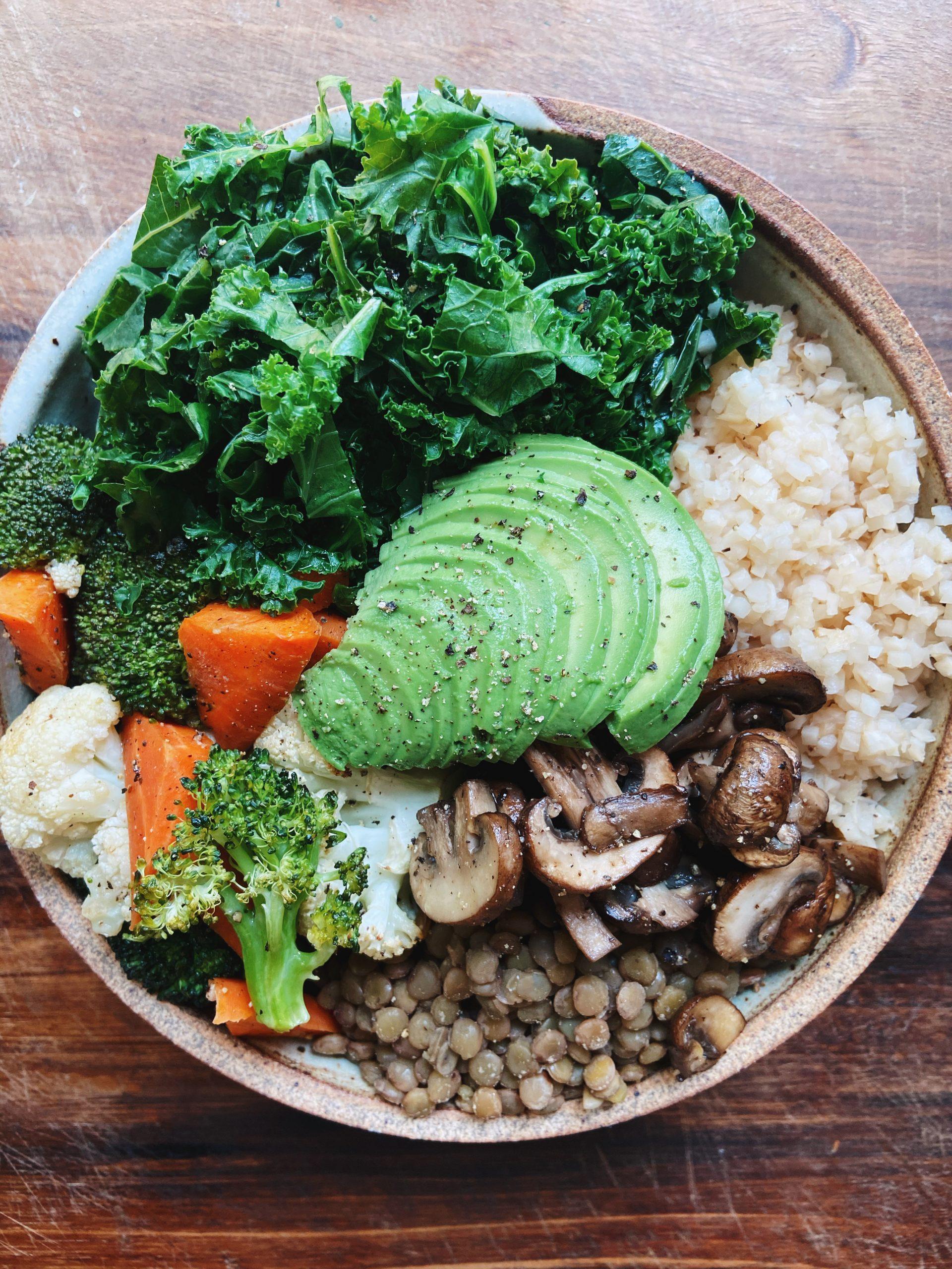 buddha bowl with kale, brown rice, lentils, mushrooms, roasted veggies and avocado