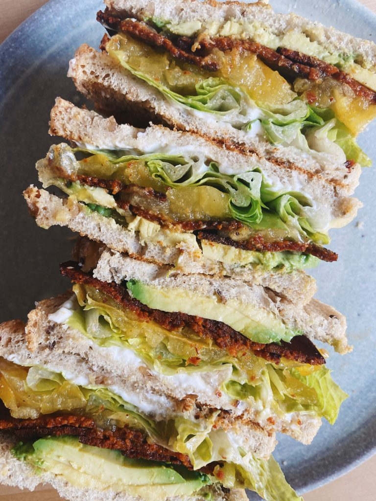 sandwiches with vegan bacon, vegan mayo, tomatoes, avocado and lettuce