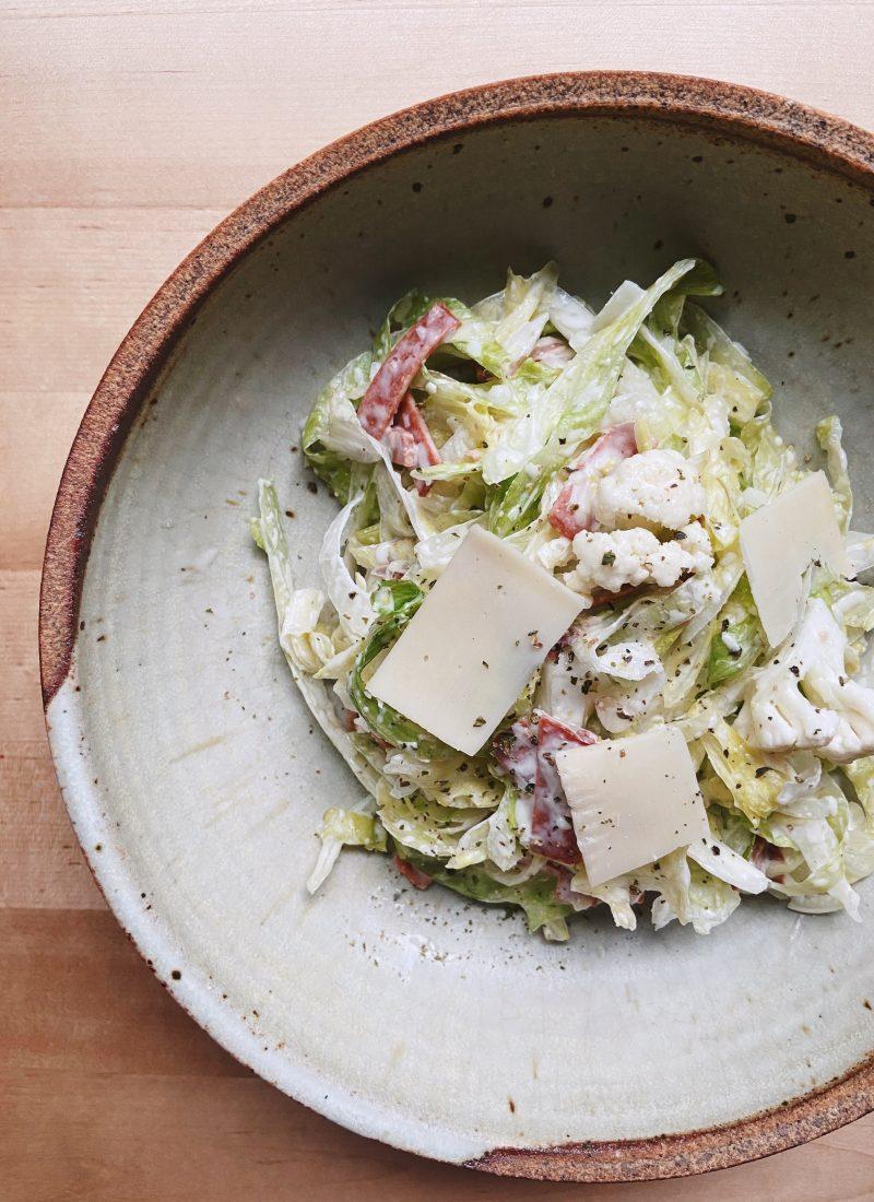 iceberg, vegan bacon, parmesan, cauliflower salad on a plate