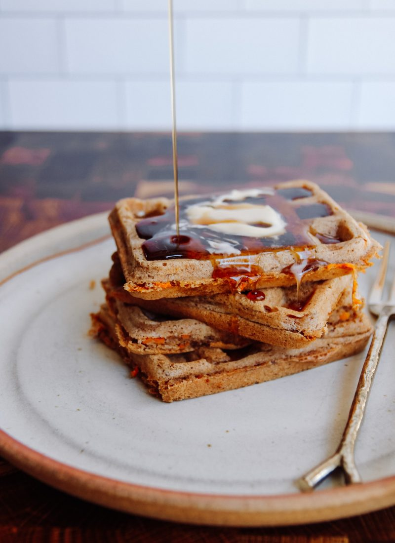 stack of waffles on a plate with syrup drizzled on top