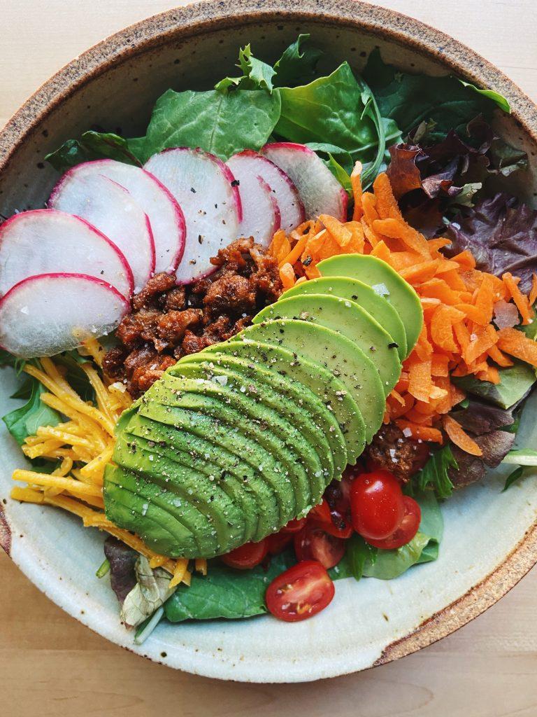 vegan taco salad with avocado, carrots, cherry tomatoes, vegan ground beef, radishes, and vegan cheese